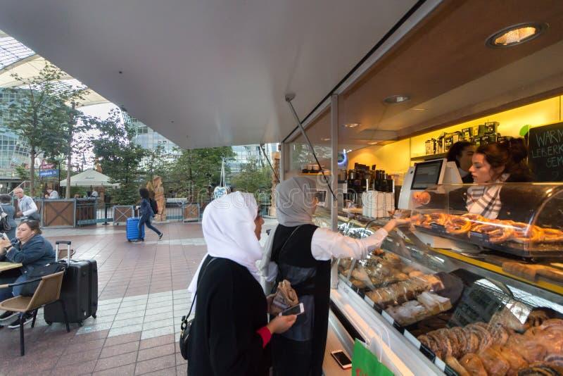 Twee moslimvrouwen die koffie kopen bij een bakkerij stock foto's