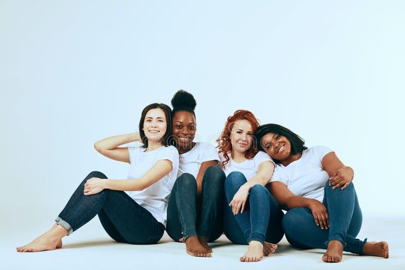 Twee multiculturele paren van vrouwen in het toevallige kijken gelukkig samen op wit stock afbeelding