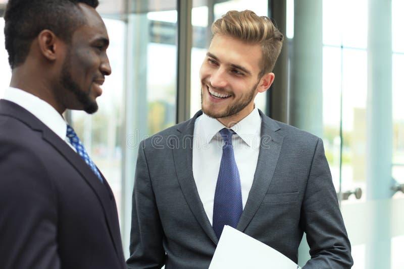 Twee multinationale jonge zakenlieden die zaken bespreken op vergadering in bureau royalty-vrije stock afbeelding