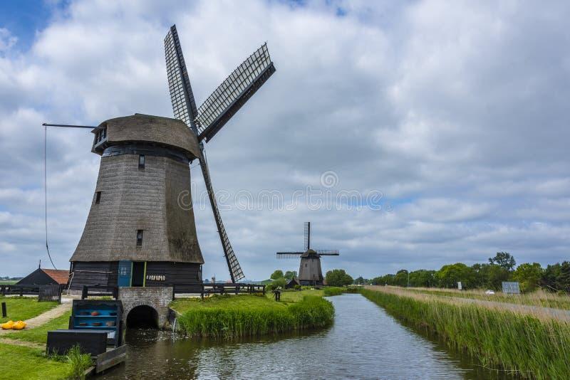 Twee Nederlands windmolens en kanaal Oterleek Nederland Holland stock foto