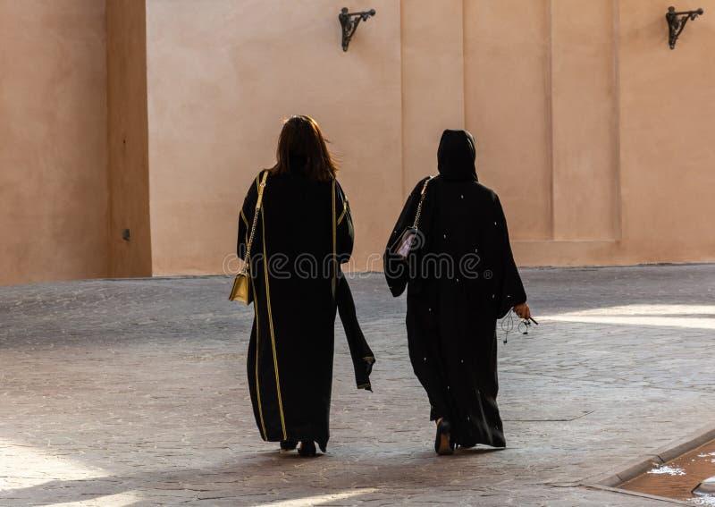 Twee niet identificeerbare Arabische vrouwen die traditionele Islamitische zwarte kleding dragen die weggaan royalty-vrije stock foto