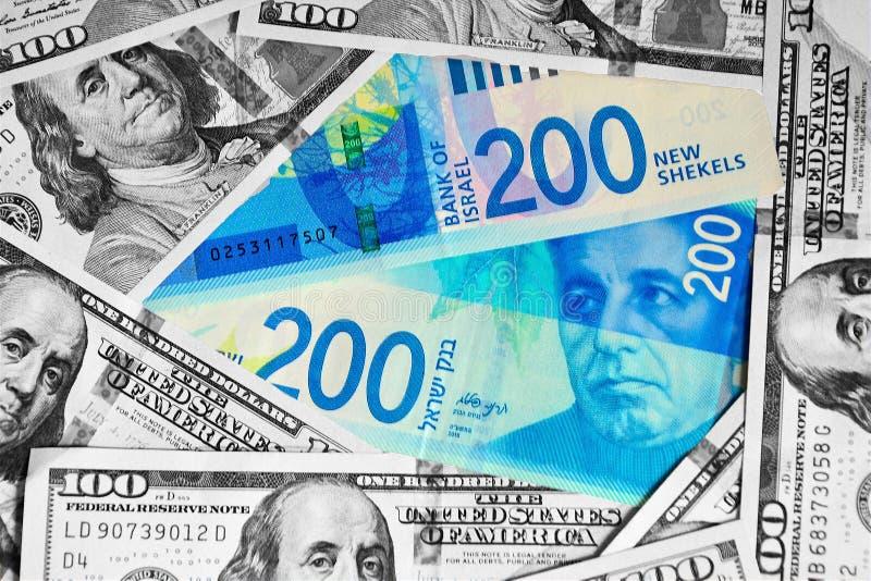 Twee nieuwe rekeningen van 200 sjekels zijn op de achtergrond van dollar 100 Contant geldachtergrond van zwart-witte dollarrekeni stock fotografie