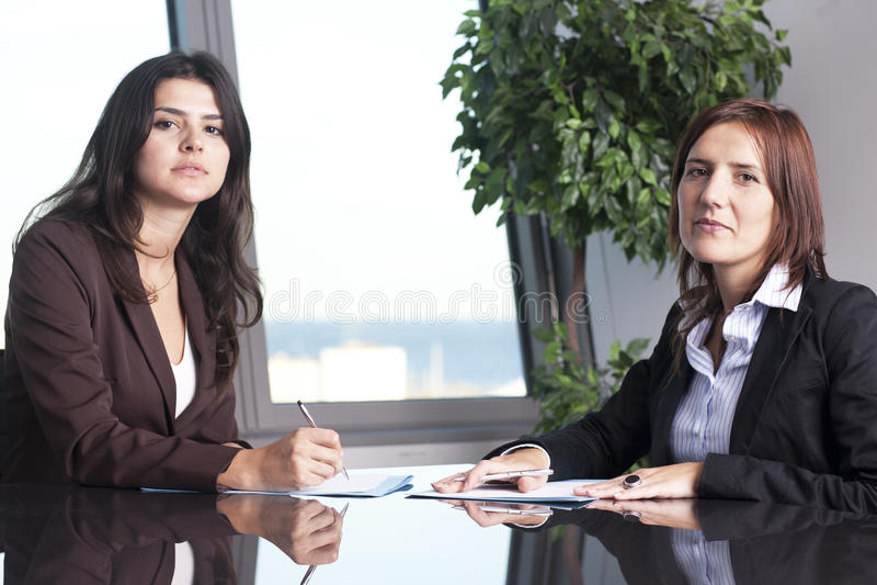 Twee onderneemsters die bij bureau zitten stock foto's