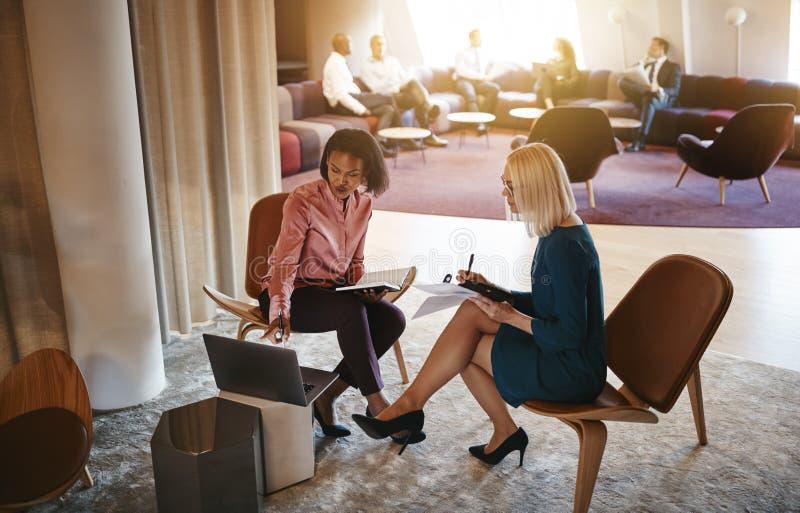 Twee onderneemsters die samen over laptop in een bureau spreken royalty-vrije stock fotografie