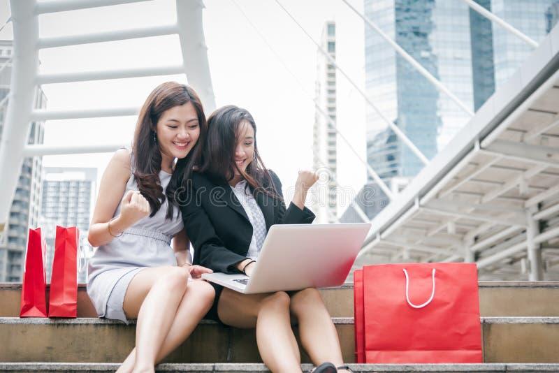 Twee onderneemsters online het winkelen laptop computer met succesvolle emotie Bedrijfsondernemer die Internet en het maken gebru stock foto