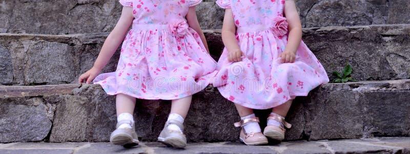 Twee onherkenbare tweelingmeisjes die op treden zitten royalty-vrije stock foto's