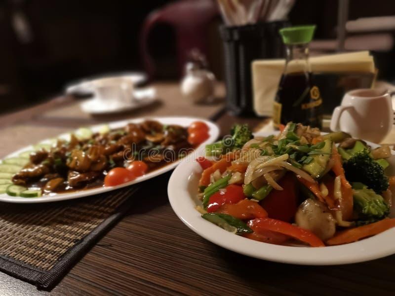 Twee oosterse schotels met rundvlees, kip, tomaten, wortelen, Spaanse peper en rijstnoedels stock foto's