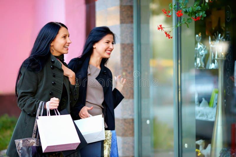 Twee opgewekte gelukkige vrouwen die in winkelvenster kijken stock fotografie