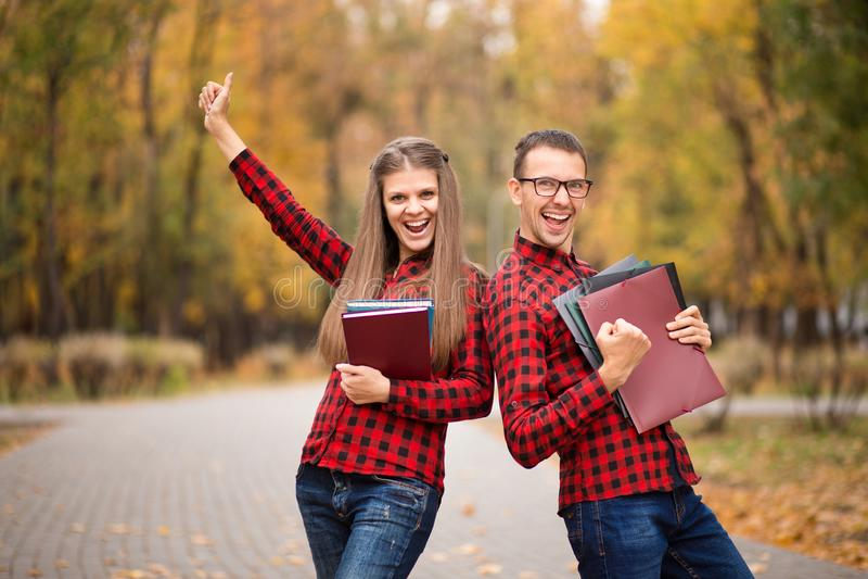 Twee opgewekte studenten met handen omhoog en erkende examens in de herfst stock fotografie