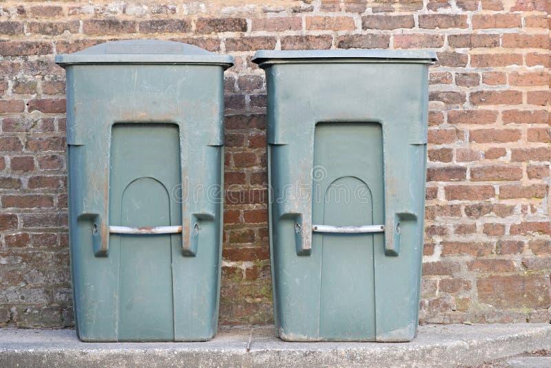 Twee oude groene afvalbakken naast een bakstenen muur royalty-vrije stock fotografie