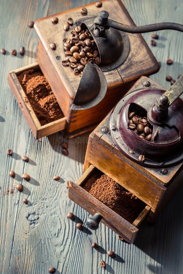 Twee oude koffiemolennen op houten lijst stock afbeeldingen