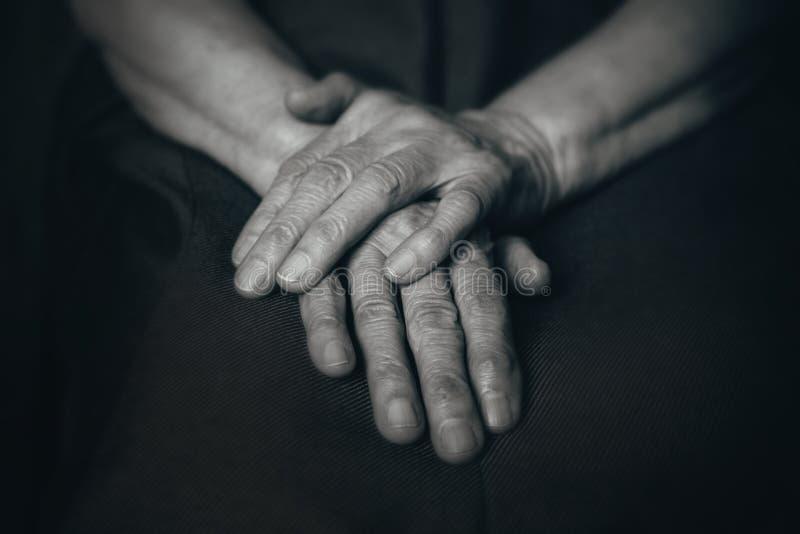 Twee oude man handen op knieën stock afbeeldingen