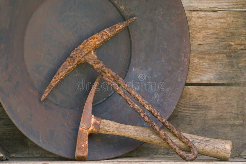 Twee oude mijnbouwoogsten en gouden pan op plank royalty-vrije stock foto's