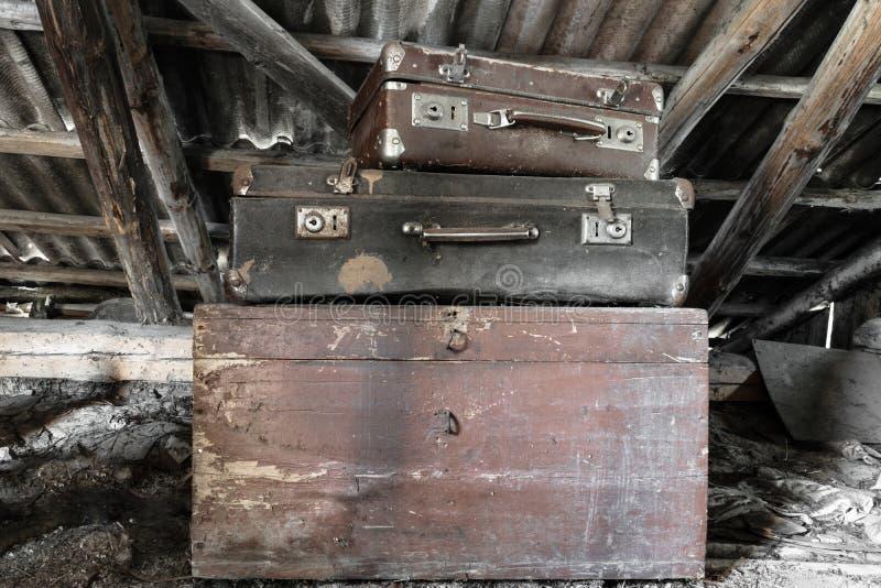 Twee Oude, Roestige, Stoffige en Vuile Koffers die op de Bruine Borst in Zolder liggen royalty-vrije stock foto