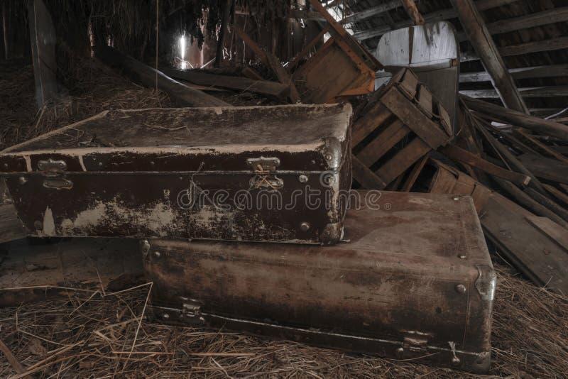 Twee oude, roestige, stoffige en vuile koffers die in zolder op hooistro liggen stock foto