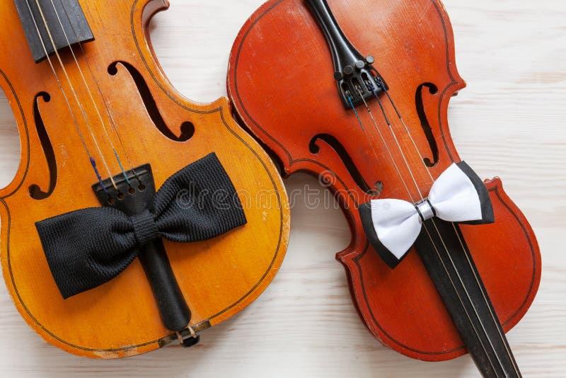 Twee Oude violen en twee vlinderdassen op de witte houten achtergrond Hoogste mening, close-up stock fotografie