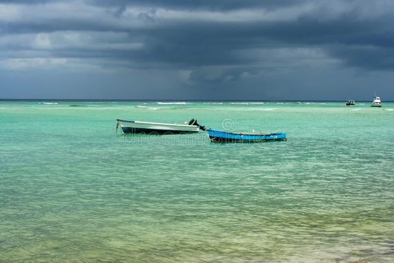Twee oude vissersboten in duidelijke overzees met een stormachtige achtergrond stock foto