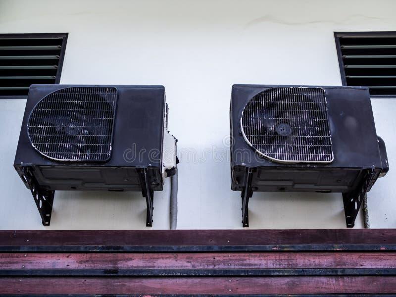Twee oude zwarte airconditionercompressoren op witte muur royalty-vrije stock afbeelding