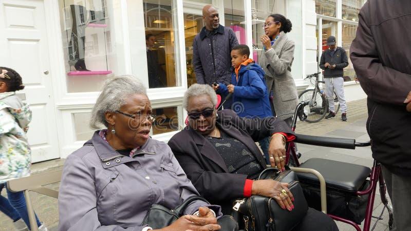 Twee oude zwarte Caraïbische dames gezet op bank het spreken Londen royalty-vrije stock foto
