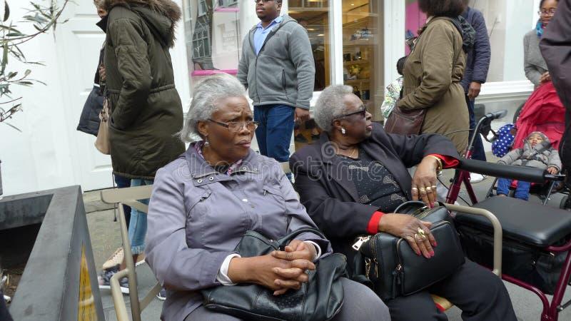 Twee oude zwarte Cara?bische dames gezet op bank het spreken Londen royalty-vrije stock afbeelding