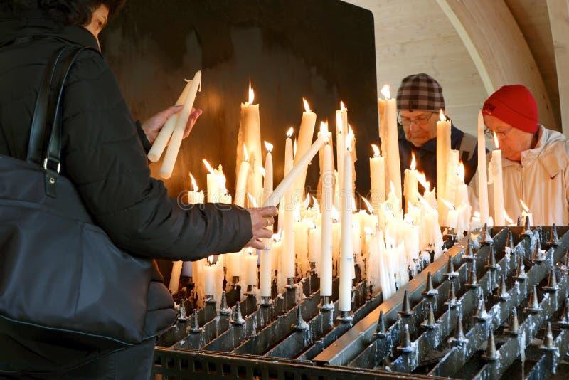 Twee oudere en één middenleeftijdsgebeden die kaarsen in kerk in brand steken royalty-vrije stock afbeeldingen