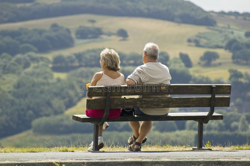 Twee oudere mensen die op een bank zitten stock afbeeldingen