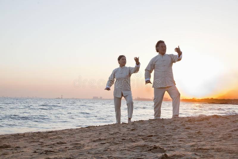 Twee oudere mensen die Taijiquan op het strand bij zonsondergang, China uitoefenen royalty-vrije stock foto's