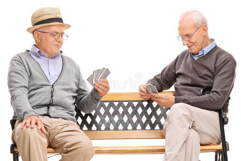 Twee oudere mensenspeelkaarten gezet op een bank royalty-vrije stock foto's