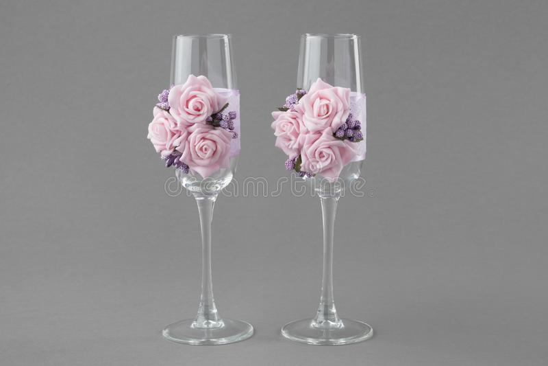 Twee overladen die glazen van de huwelijkswijn met kant en roze rozen worden verfraaid stock afbeeldingen