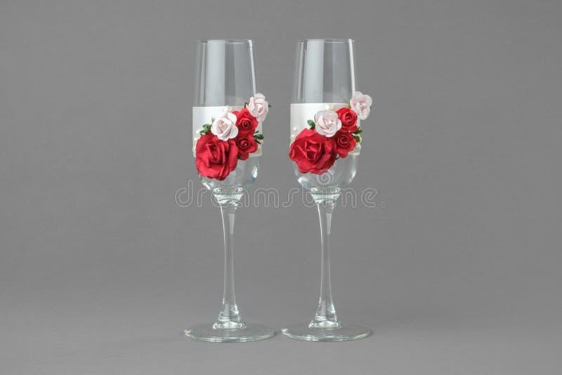 Twee overladen die glazen van de huwelijkswijn met rode en roze rozen worden verfraaid stock fotografie