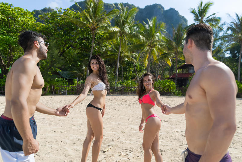 Twee Paar op de Vakantie van de Strandzomer, Jongeren die in Liefde, Man de Handen Overzeese van de Vrouwenholding Oceaantoevluch royalty-vrije stock afbeelding
