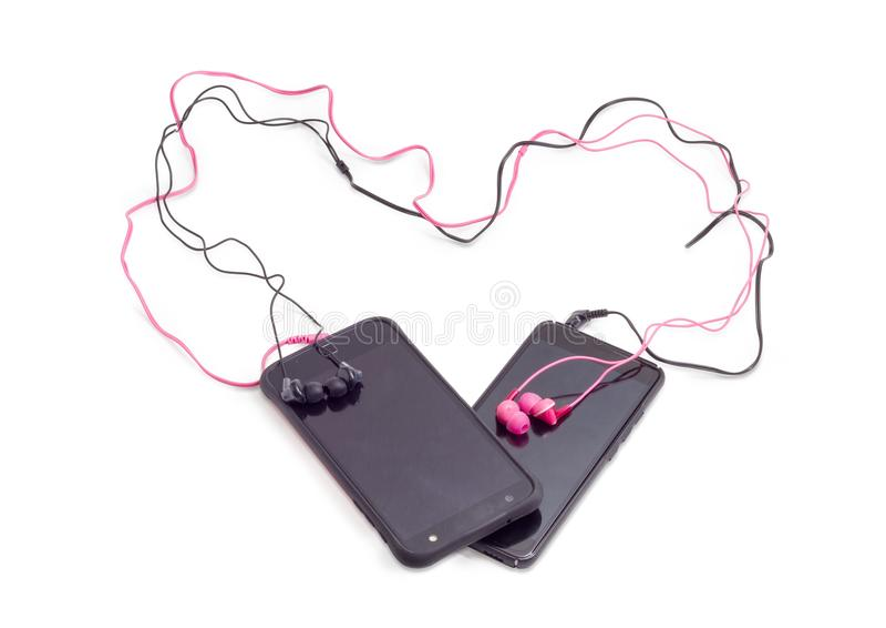 Twee paar rode en zwarte die oortelefoons aan smartphones worden aangesloten stock foto