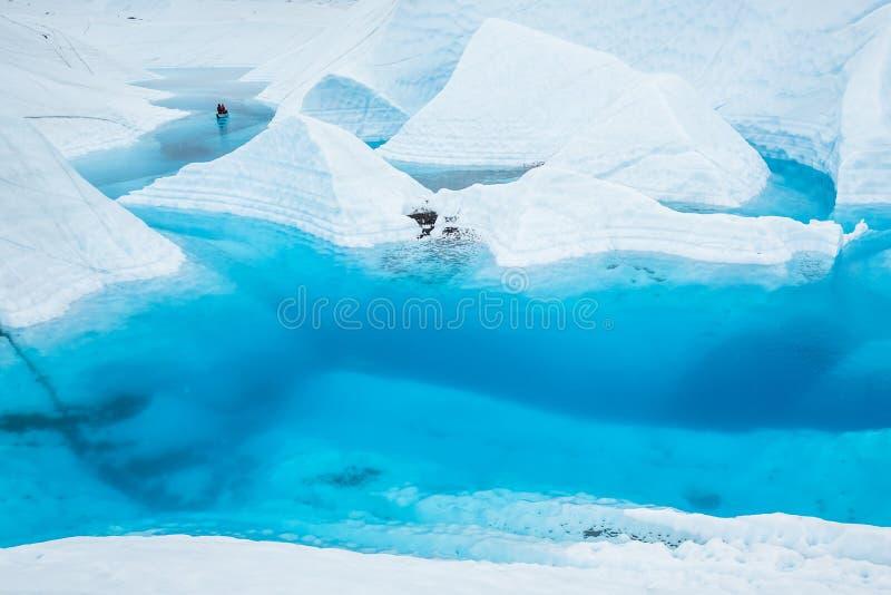 Twee paddlers in een kano op een groot blauw meer op de oppervlakte van de Matanuska-Gletsjer in Alaska royalty-vrije stock fotografie