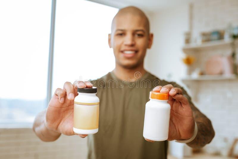 Twee pakken vitaminen in handen van professionele sportman stock foto