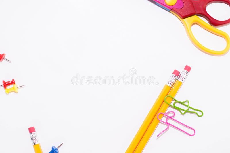 Twee paperclippen die terwijl het liggen op een witte vloer en op een potlood spreken Het miniatuurschoolleven en terug naar scho stock foto's