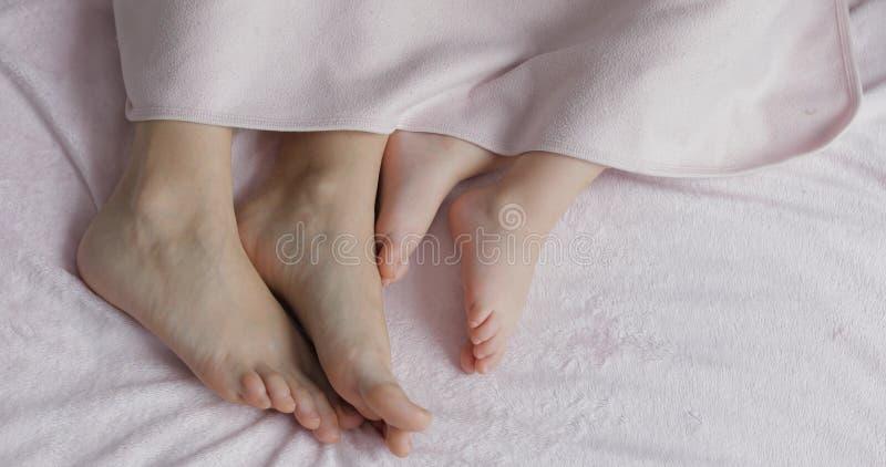 Twee paren benen van de familie in bed onder de sprei - moeder en baby royalty-vrije stock afbeelding