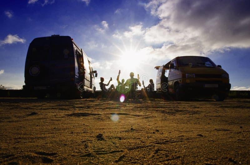 Twee paren die de zomer van partij op het strand naast therbestelwagens genieten stock afbeelding