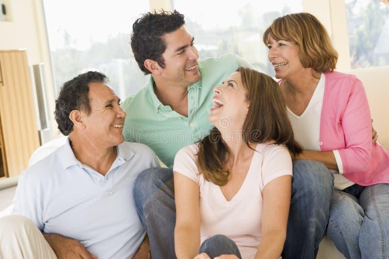 Twee paren die in woonkamer het glimlachen zitten   royalty-vrije stock afbeeldingen