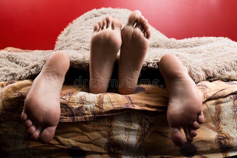 Twee paren mannelijke en vrouwelijke die voeten van onder de deken worden gezien slaap samen, minnaars die geslacht hebben royalty-vrije stock afbeelding