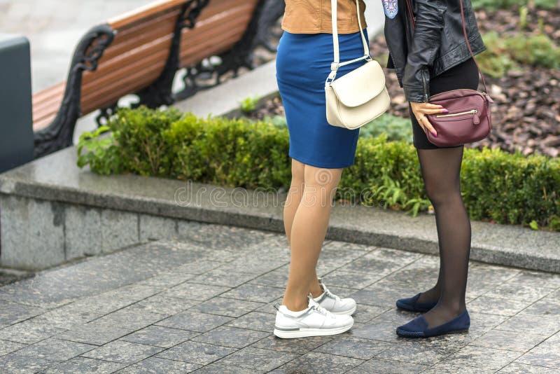 Twee paren slanke meisjesbenen in korte rokken, witte leertennisschoenen en comfortabele de zomerschoenen op laag platform Manier stock foto's