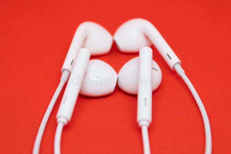 Twee paren witte hoofdtelefoons dicht bij elkaar op rode achtergrond, één paar oortelefoons is vaag stock fotografie