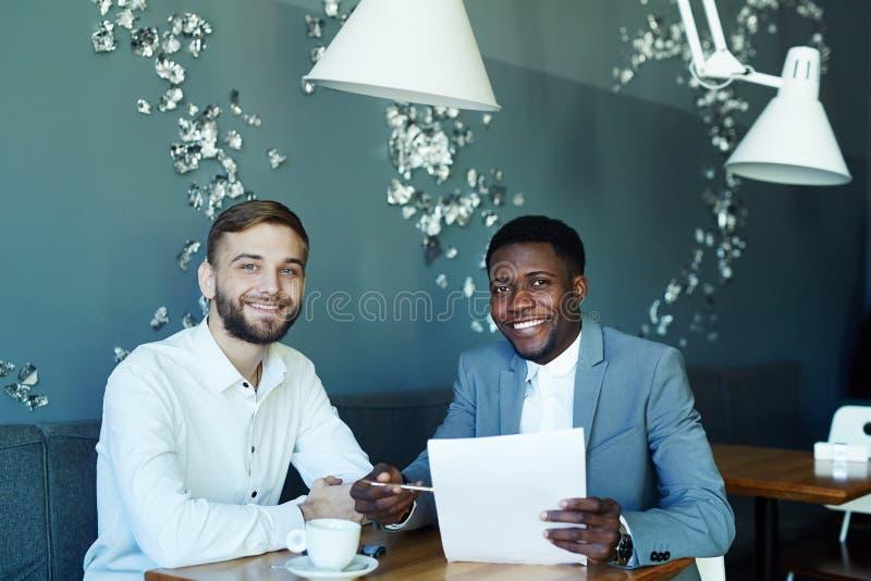 Twee Partners die in koffie glimlachen stock foto