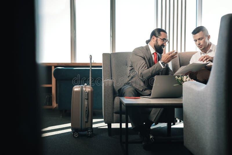 Twee partners die op bank in hotelhal dichtbij hun bagage zitten stock afbeelding