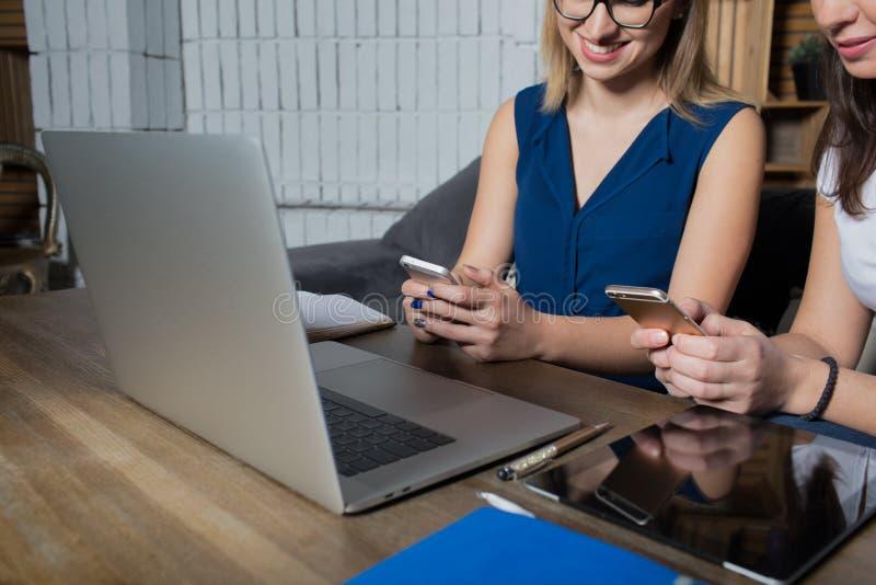 Twee partners die op cellphones in sociaal netwerk babbelen terwijl het wachten van videovraag op laptop computer royalty-vrije stock fotografie