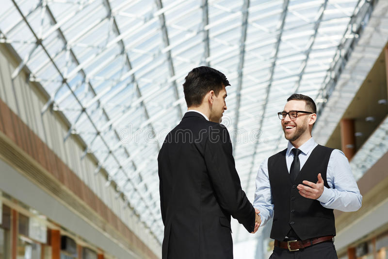 Twee Partners die in Zaal van de Moderne Bureaubouw samenkomen royalty-vrije stock foto