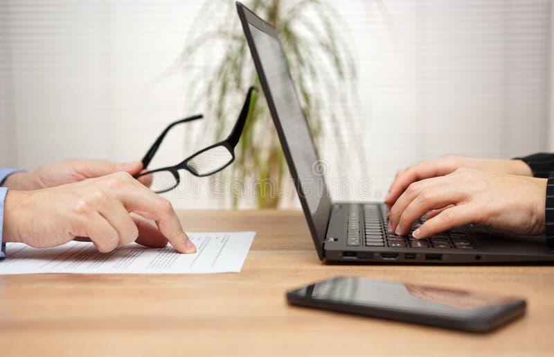 Twee partners onderzoeken en herzien document in bureau, wom stock foto's