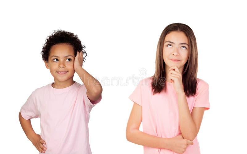Twee peinzende kinderen die omhoog kijken stock foto's