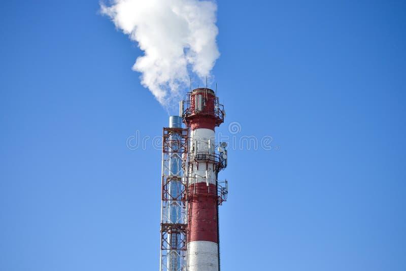 Twee pijpen Industriële rook van een schoorsteen tegen de hemel stock afbeelding