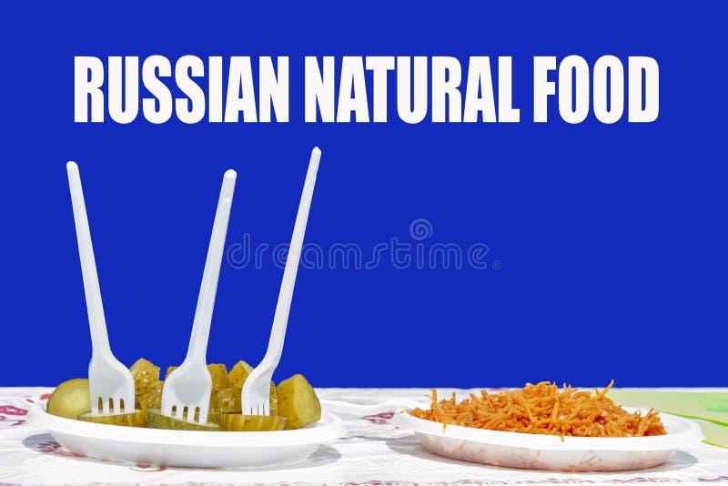 Twee plastic platen met voedsel In één, gesneden gezouten komkommers en drie plastic vorken, in de andere geraspte wortelen royalty-vrije stock afbeelding