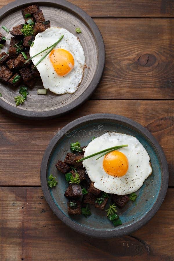 Twee platen met gebraden eieren en brood, rustieke stijl stock fotografie